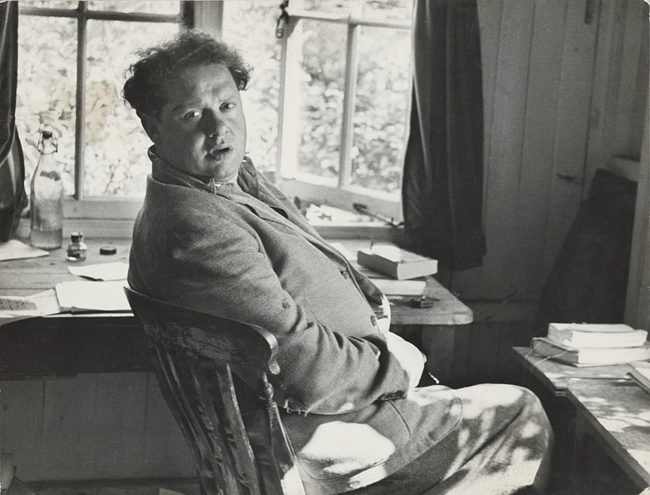Dylan sitting in chair near tables with books and open window