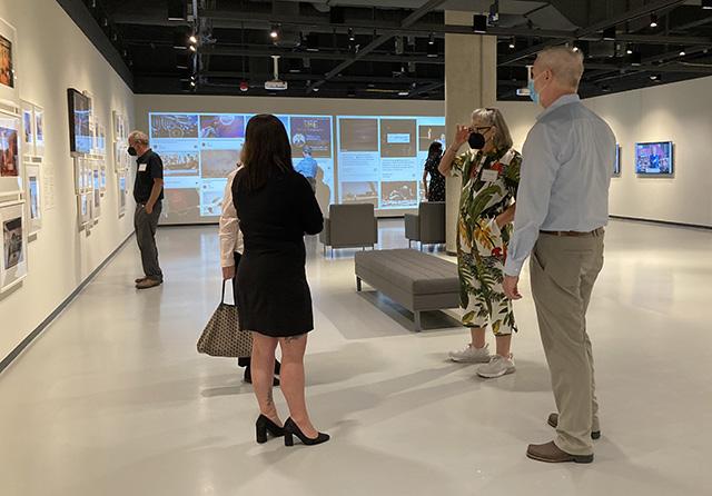 Members standing in gallery talking